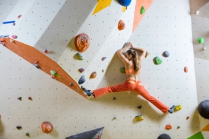 Young woman climbing challenging bouldering route. In climbing gym.